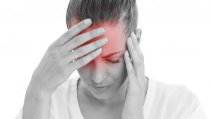 Woman having a headache with her head in her hands on white back